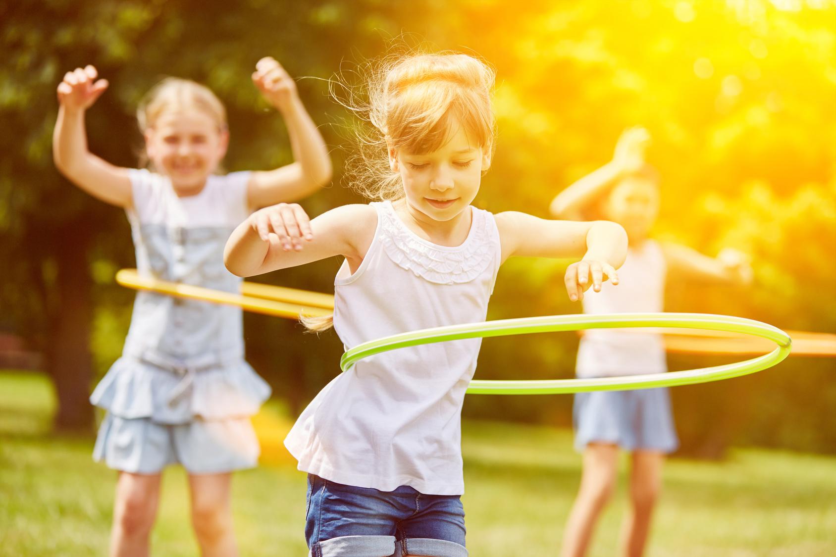 Kinder spielen im Sommer mit Hula-Hoop-Reifen (Foto: fotolia.de © Robert Kneschke)